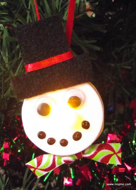 I wanted the mouth to have more dimension so I used some black acrylic paint over the Sharpie dots. The snowman is very cute, but not very photogenic when the tealight is turned on.